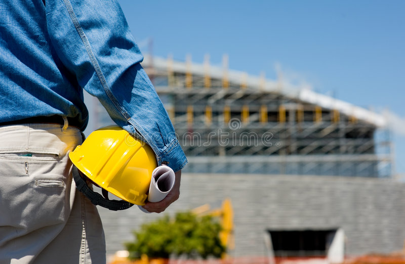 Construction Worker at Site. A construction worker or foreman at a construction site observing the progress of construction job or project, with copy space royalty free stock images