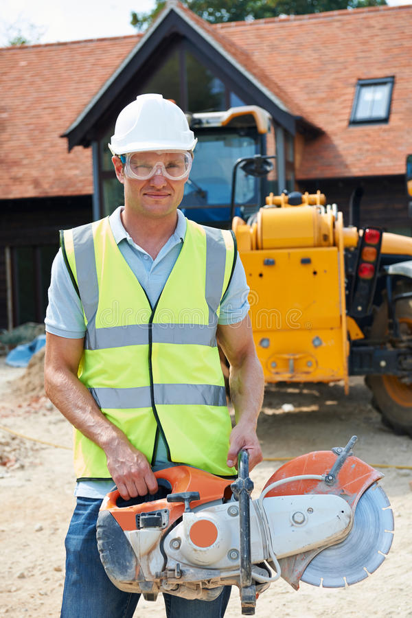 Construction Worker On Site Holding Circular Saw royalty free stock photography