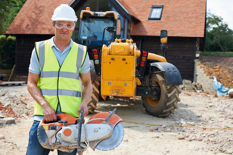 Construction Worker On Site Holding Circular Saw royalty free stock photos