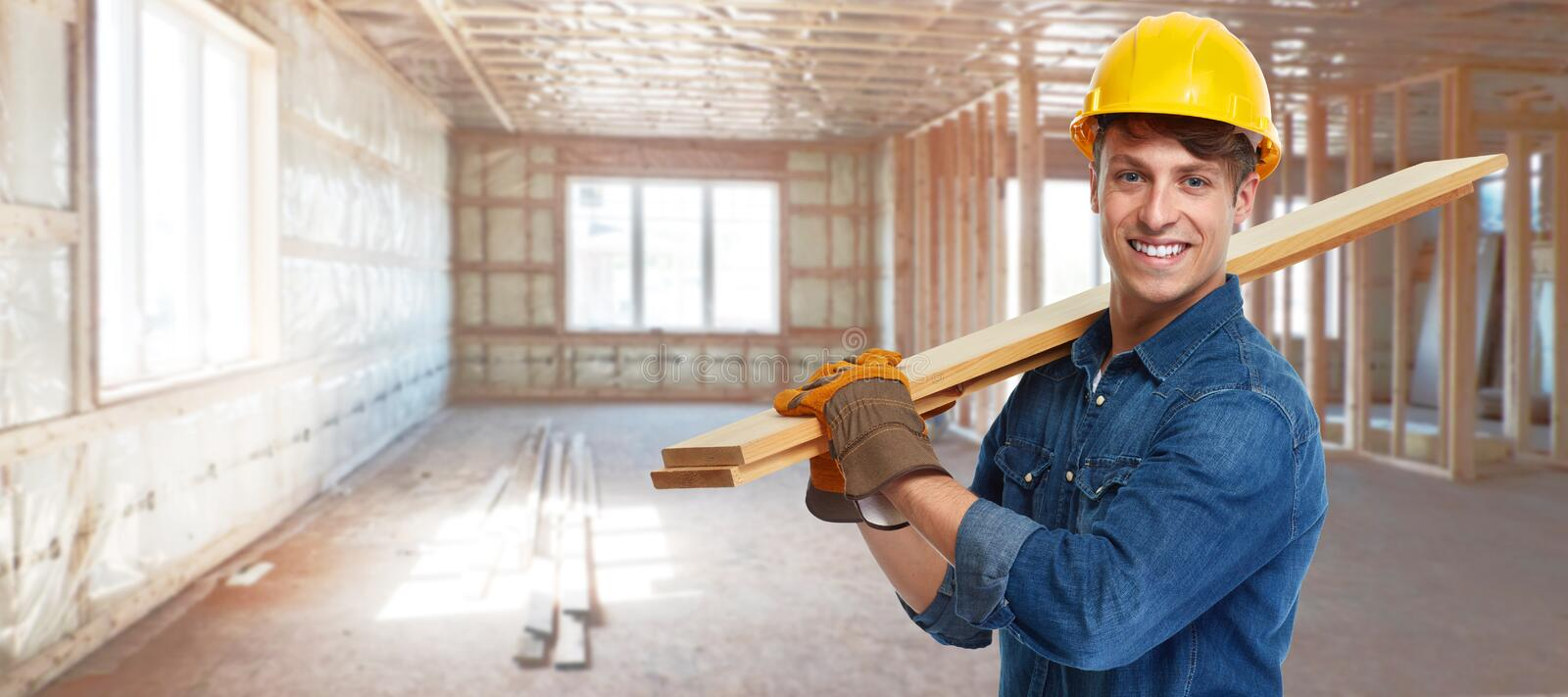 Construction worker. Smiling professional construction worker with wooden plank stock photography