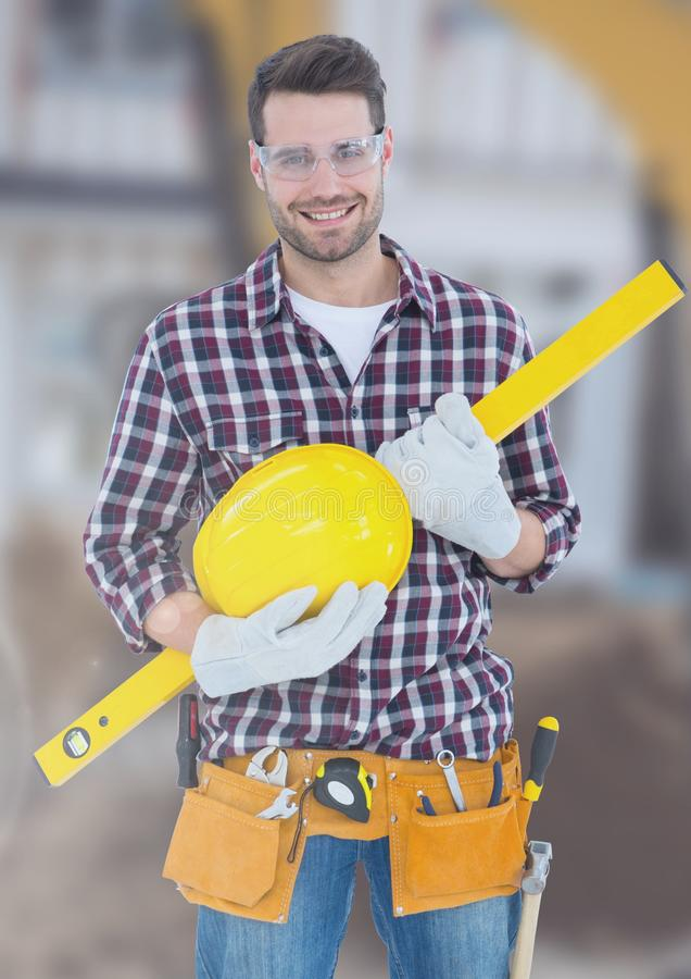Construction Worker with spirit level in front of construction site stock photo