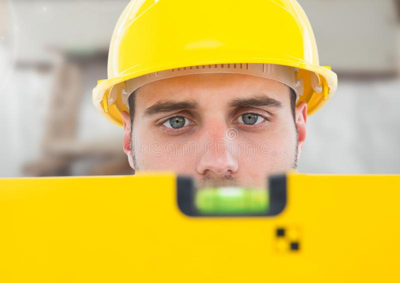 Construction Worker with spirit level in front of construction site royalty free stock photo