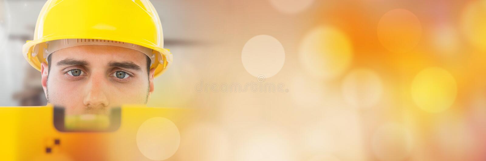 Construction Worker with spirit level in front of construction site with sparkling lights bokeh tran stock images