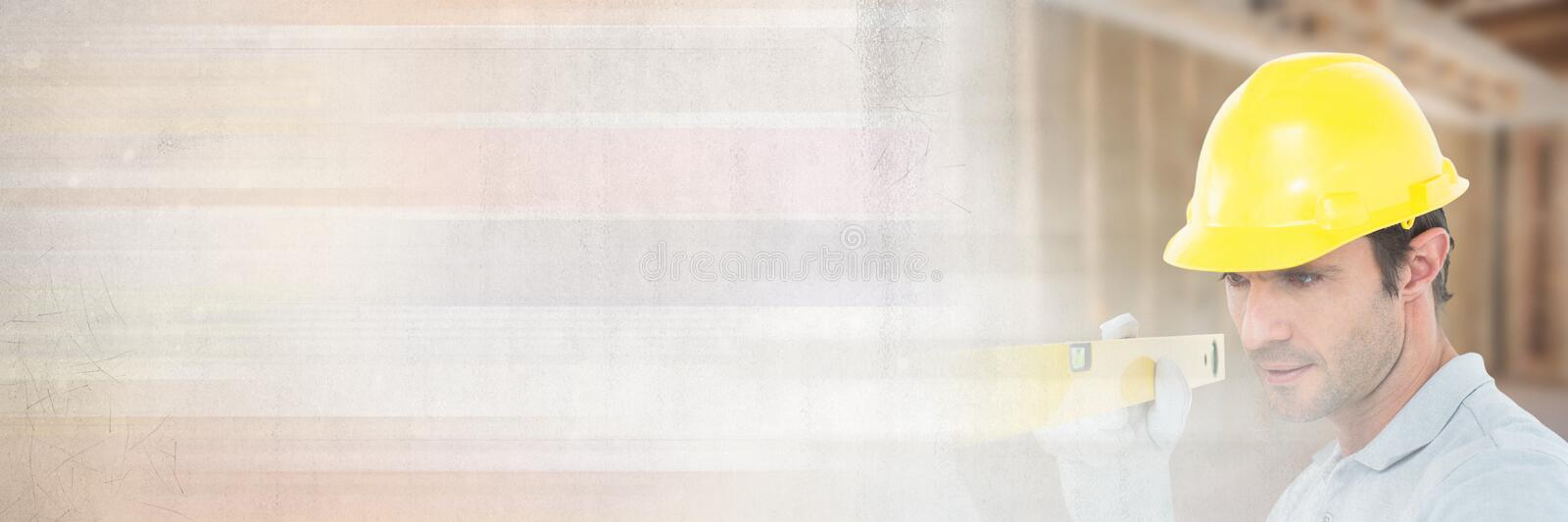 Construction Worker with spirit level in front of construction site with transition effect stock photo