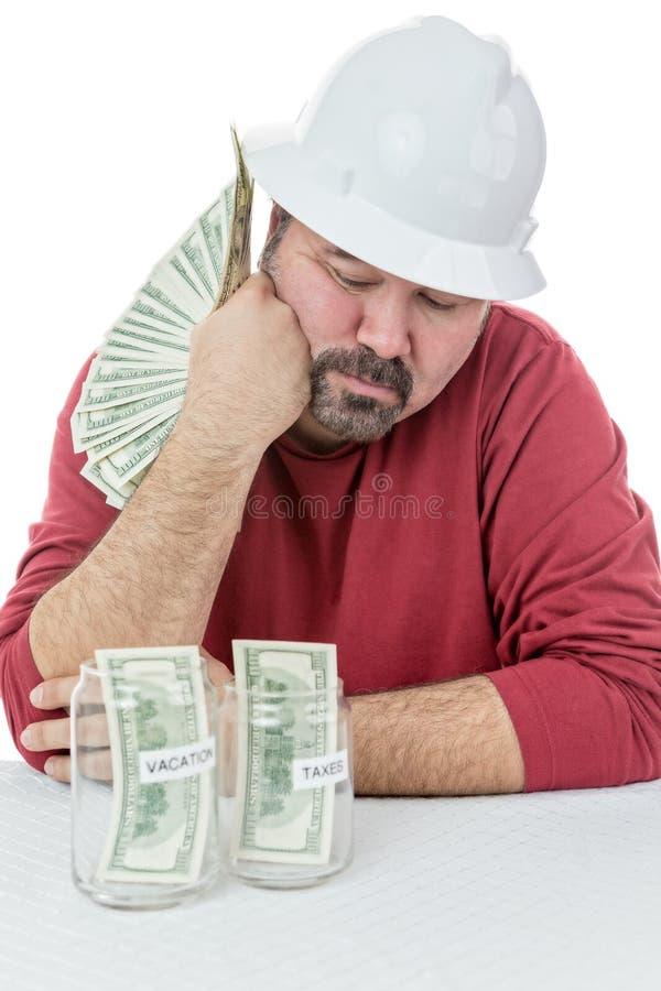 Construction worker splitting money stock image