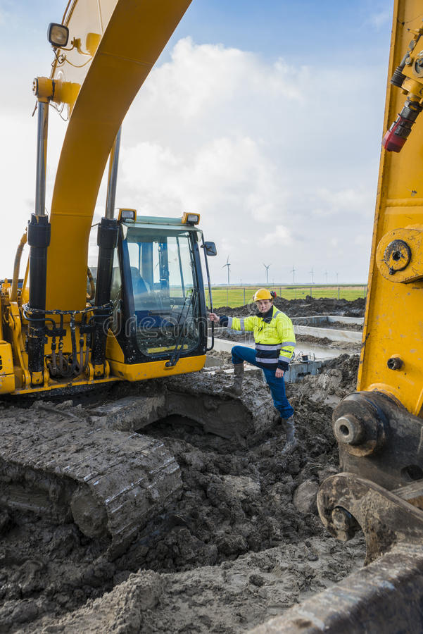 Construction worker standing proudly next to his excavator stock photography