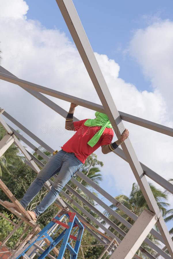 Construction worker straddling a steel beam of a building. Construction worker straddling a steel beam of a house building royalty free stock photos