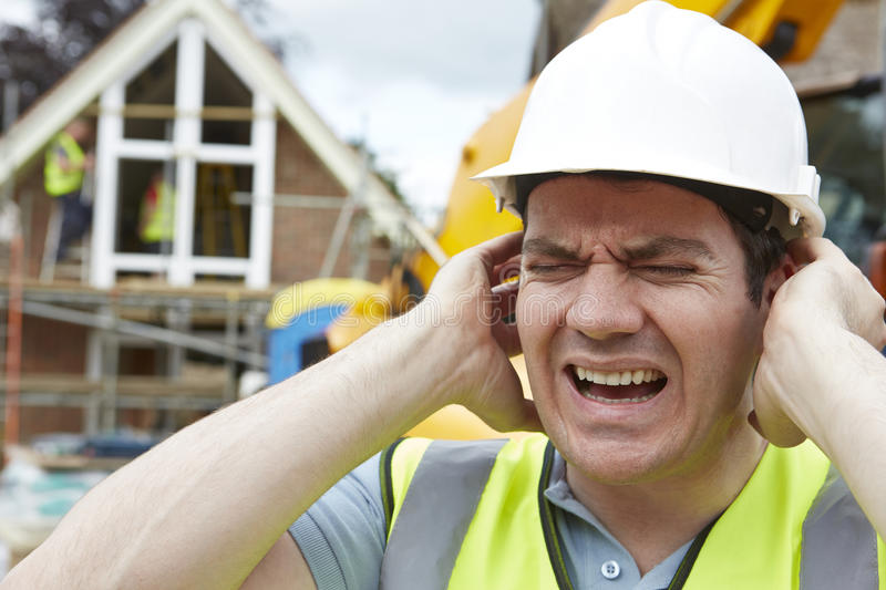 Construction Worker Suffering From Noise Pollution On Building Site. Worker Suffering From Noise Pollution On Building Site royalty free stock images