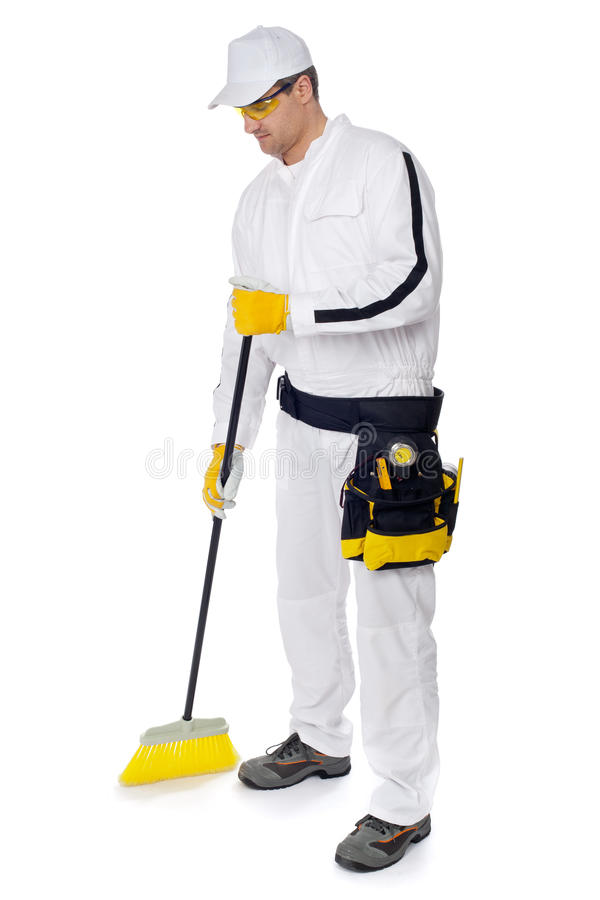 Construction worker sweeping with a broom floor stock photos