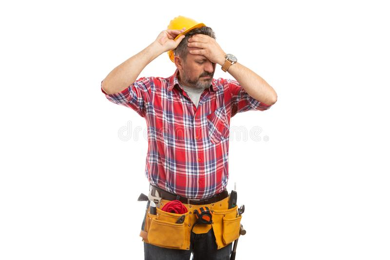 Construction worker taking off hardhat as headache gesture royalty free stock images