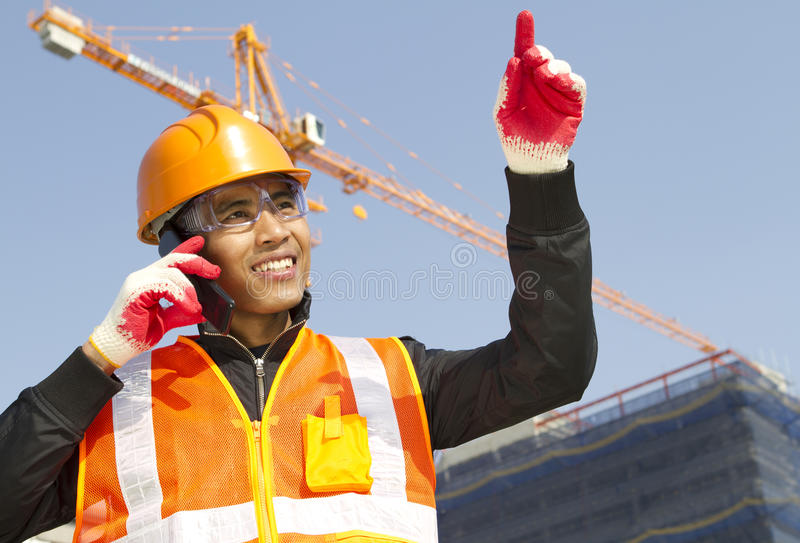 Construction worker with crane in background. Construction worker talking in mobile phone with crane in background stock photo
