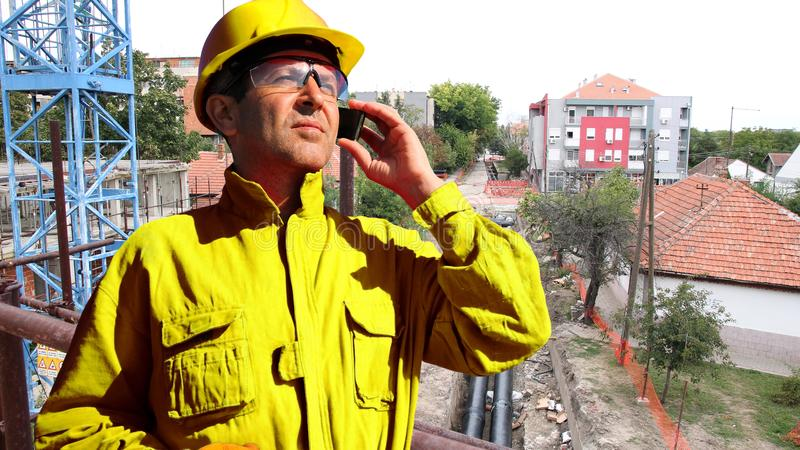Construction Worker Talking On The Smartphone At Construction Site stock image