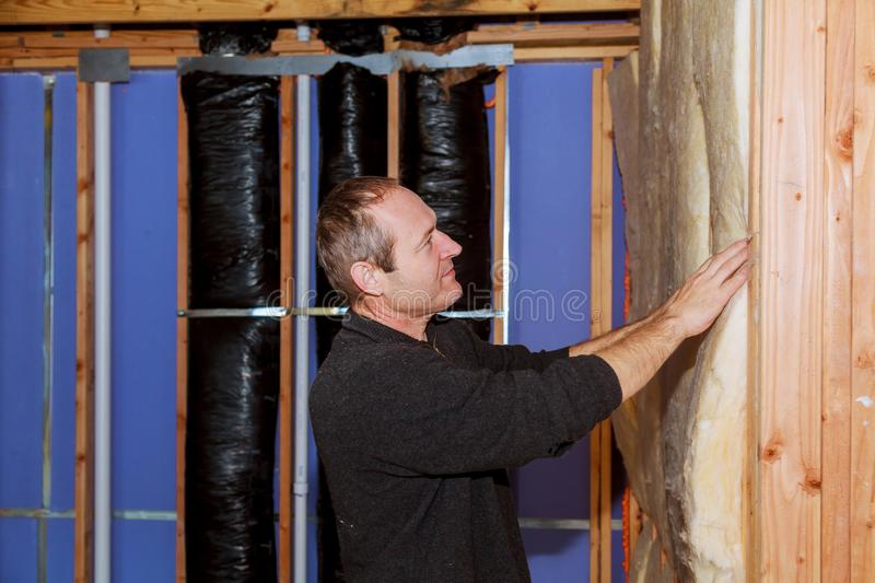 Construction worker thermally insulating house attic with glass wool stock image