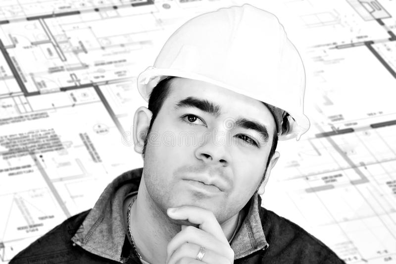 Construction Worker Thinking. A construction worker or architect wearing a hard hat has a contemplative look on his face with generic blueprints in the stock photos