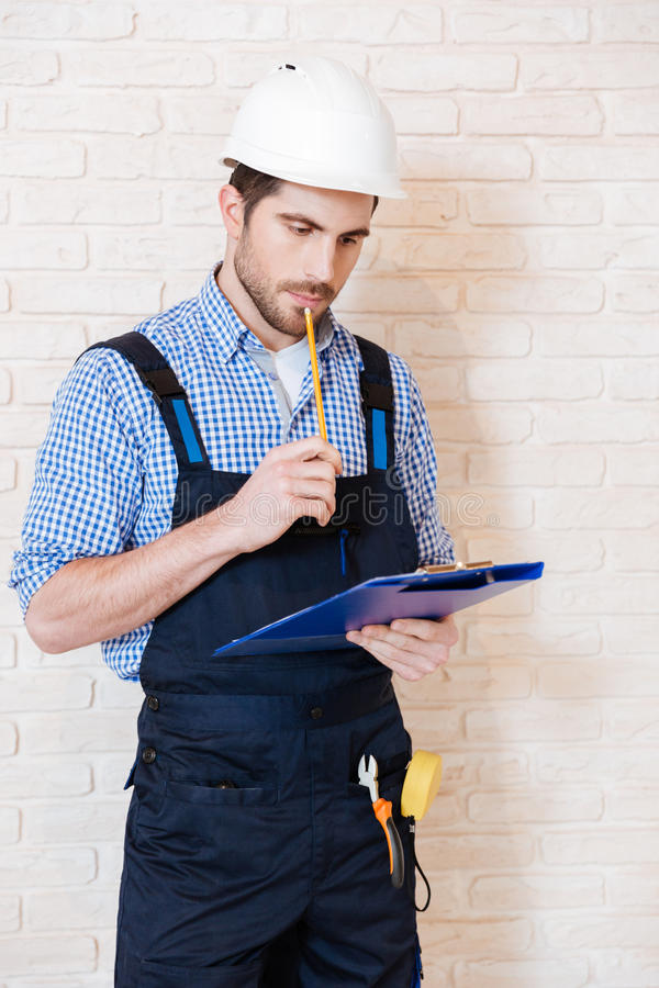 Construction worker thinking about something using clipboard royalty free stock image