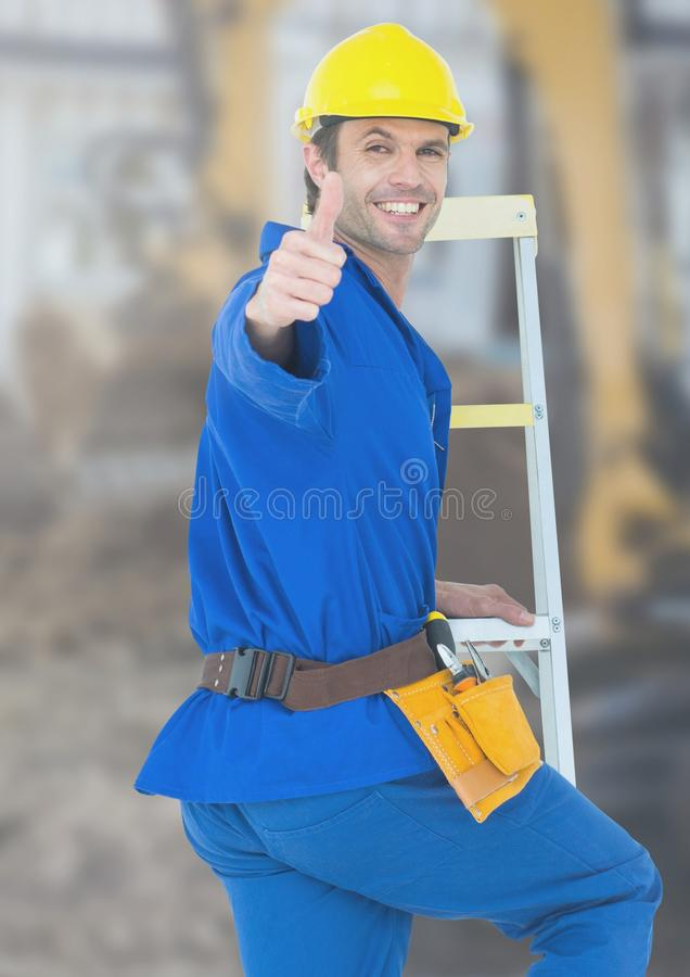 Construction Worker with thumbs up in front of construction site royalty free stock images