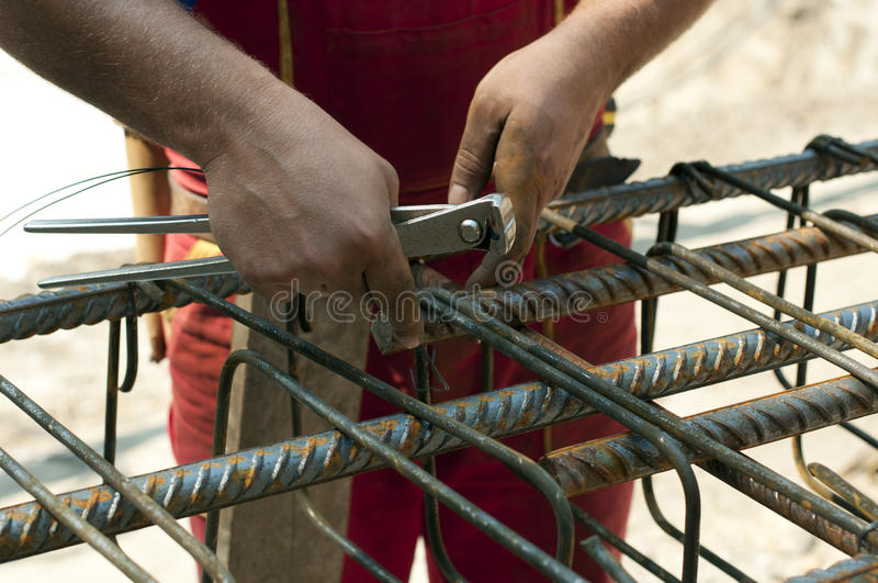 Construction worker ties reinforcing steel royalty free stock image