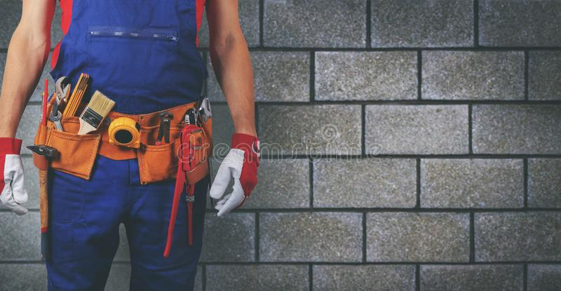 Construction worker with tool belt on block wall background royalty free stock photos