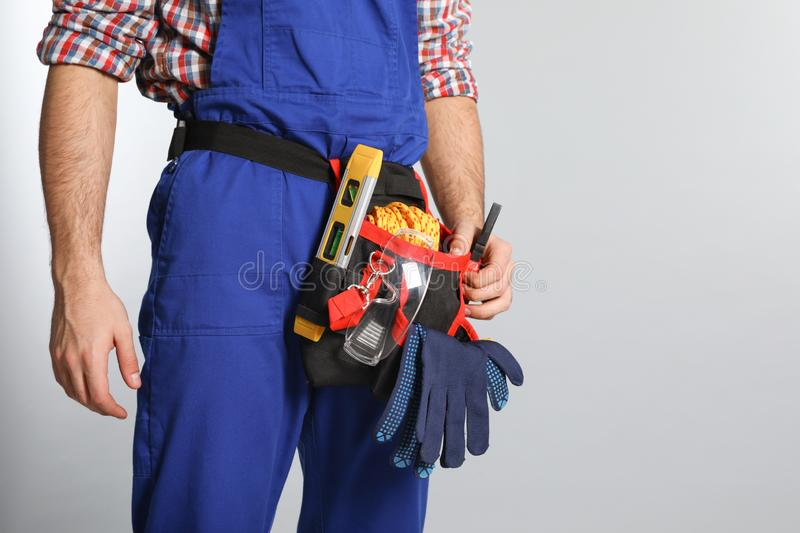 Construction worker with tool belt on light background, closeup. Space for text stock photos