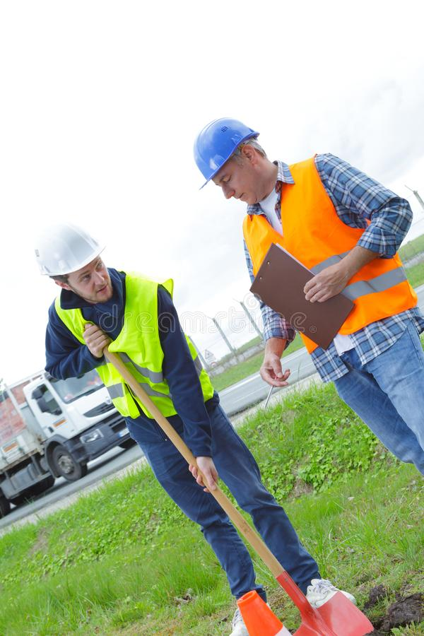 Construction worker trainee digging with shovel stock photography