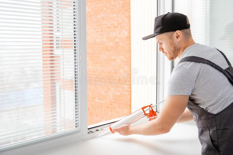 Construction worker use gun silicone tube for repairing and installing window in house royalty free stock photos