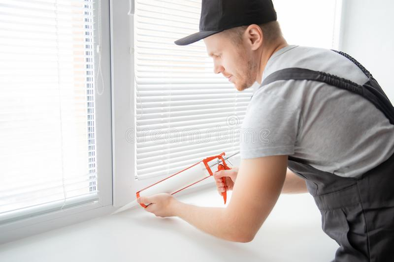 Construction worker use gun silicone tube for repairing and installing window in house stock images