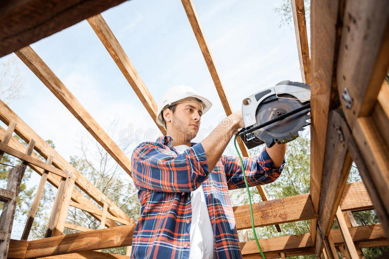 Construction Worker Using Electric Saw On Timber. Low angle view of male construction worker using electric saw on timber frame at site stock photo