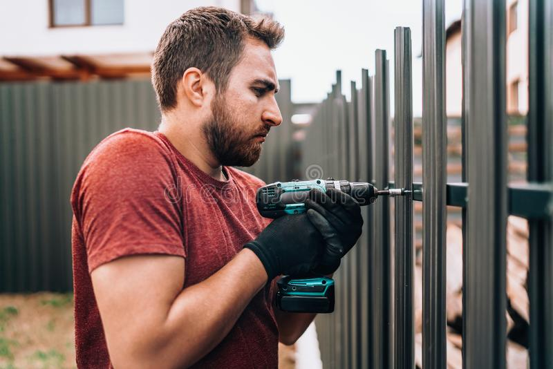 Construction worker using electrical screwdriver and mounting metal elements on fence royalty free stock photography