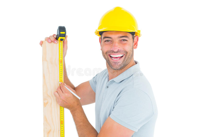 Construction worker using measure tape to mark on plank royalty free stock images