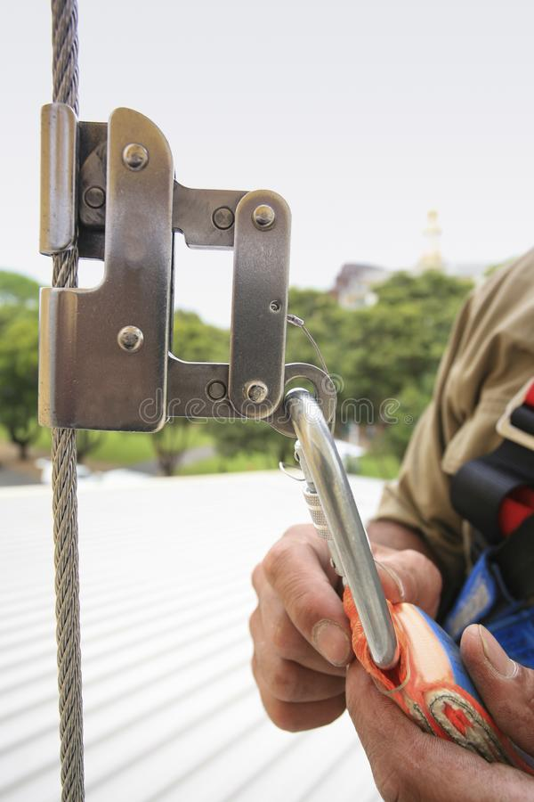 Construction worker using safety shock absorber lanyard with fall arrest, fall restraint harness protection device. And connecting into roof cable vertical line royalty free stock image
