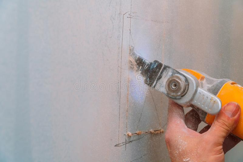 Construction worker using a sawsall tool to cut drywall a wall down to a diy house renovation. Cutting plasterboard drywall sheetrock wallboard building sawing royalty free stock photo