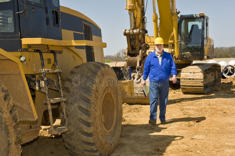 Construction Worker Walking Along Equipment royalty free stock photos