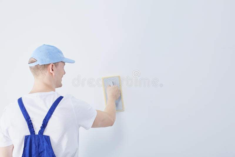 Construction worker and the wall. Young construction worker preparing the white wall in the house for painting stock image