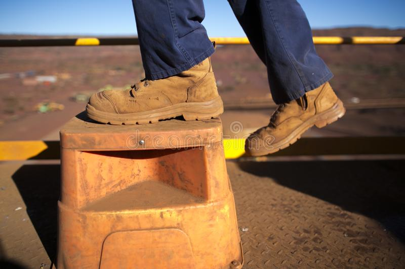 Construction worker wearing heavy duty steel cap boot using safety step white working at height stock image