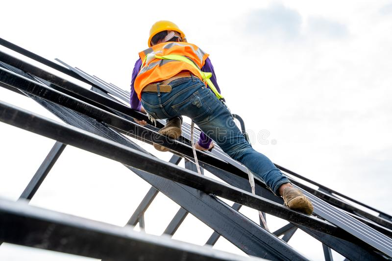 Construction worker wearing safety harness and safety line working on high roofing. royalty free stock images