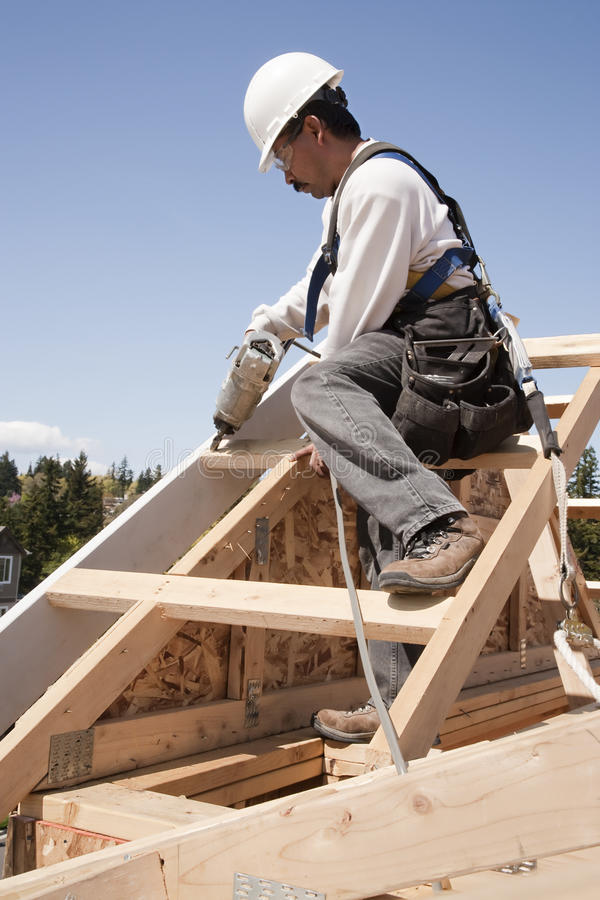 Construction Worker at Work. Construction worker fastening wooden beams on top of a partially built structure. Vertical shot stock images