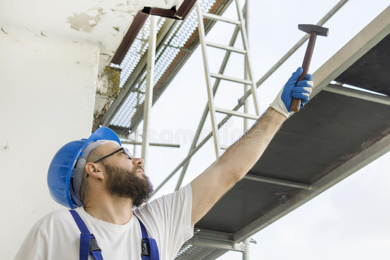 Construction worker in a work attire, protective gloves and a helmet on the head gives a hammer. Work at high altitude. Scaffold stock photo