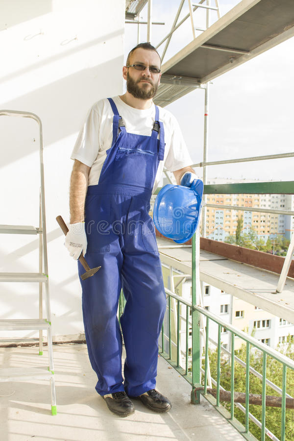 Construction worker in a work attire, protective gloves holds a helmet and a hammer. Work at high altitude. Scaffolding in the b royalty free stock photos