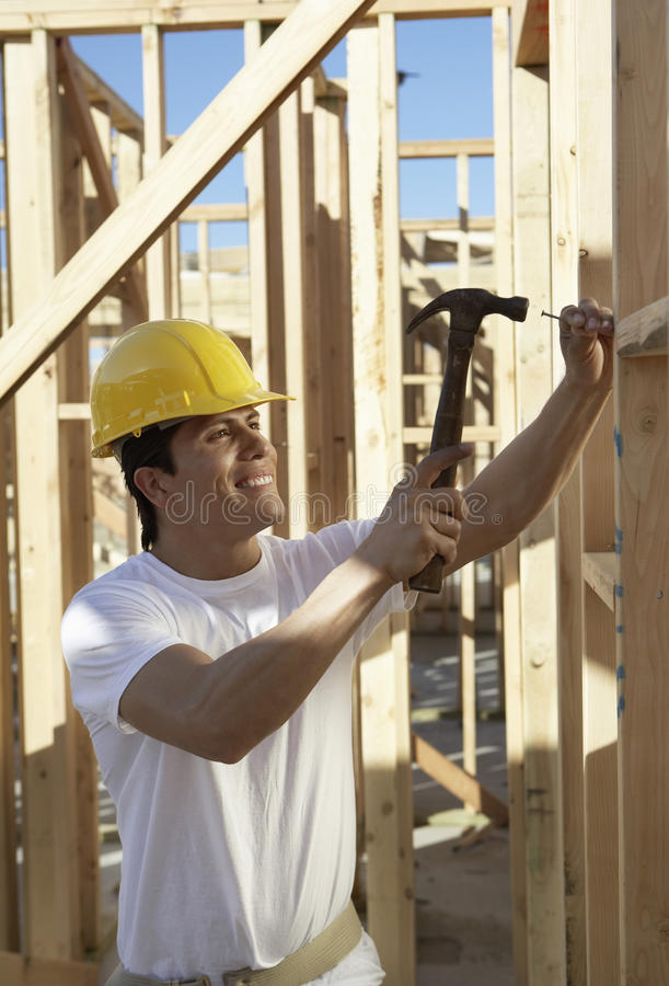 Construction Worker Working On Timber Frame. Side view of a construction worker in hardhat working on timber frame royalty free stock photo