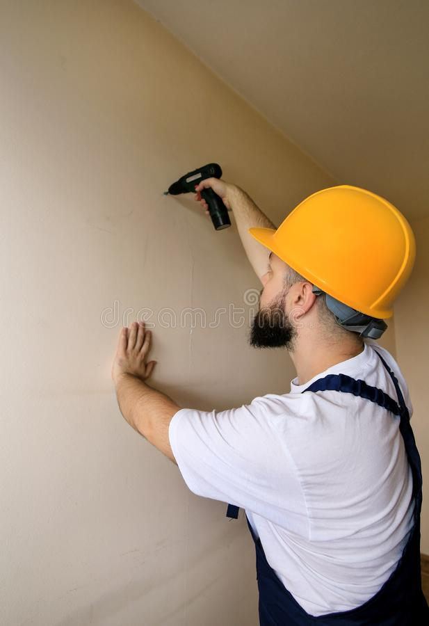 Construction worker works on renovation of apartment. Builder using electric screwdriver and screwing screw out of wall. royalty free stock photography