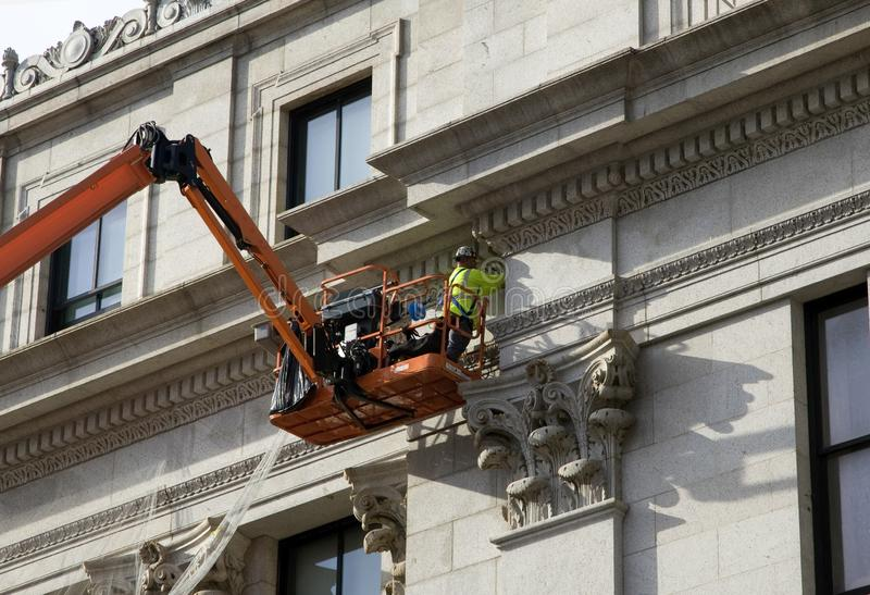 Construction worker works on side of James A Farley Post Office Building royalty free stock photography