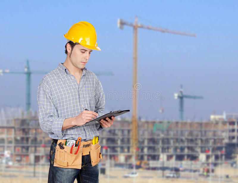 Construction worker writing paperwork. With a construction building of background royalty free stock photo