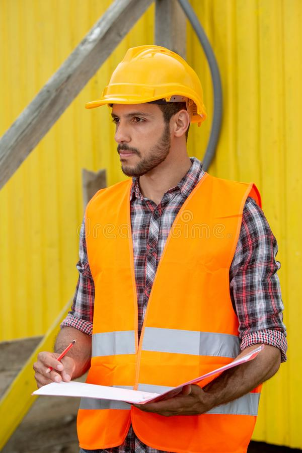 Construction worker with yellow helmet and orange vest royalty free stock images