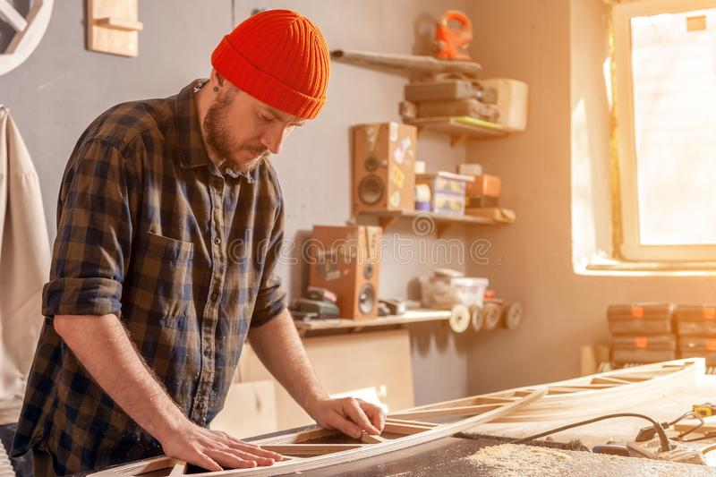 Construction Worker. A young man in a orange hat  carpenter builder in work clothes processing a wooden board with a milling machine in the workshop, around a royalty free stock photos