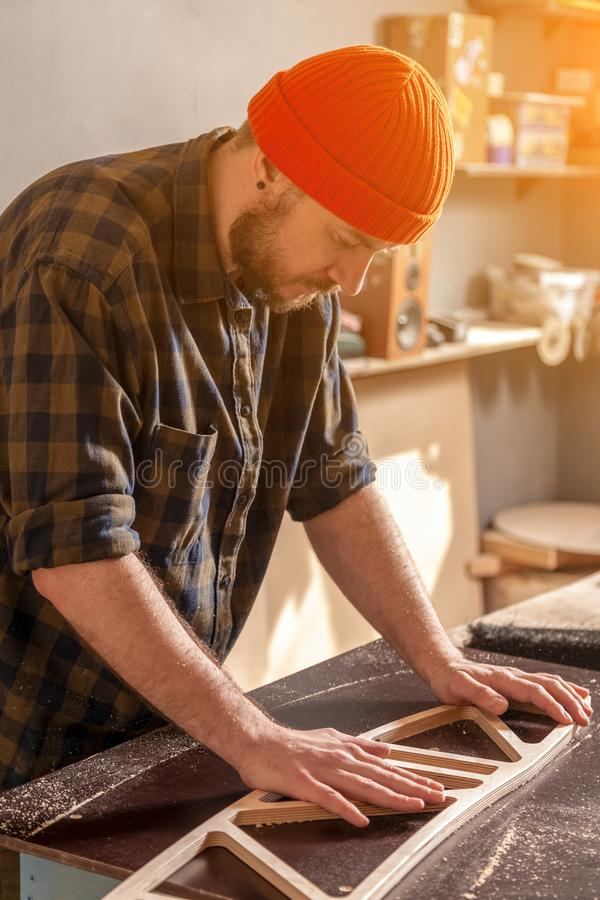 Construction Worker. A young man in a orange hat  carpenter builder in work clothes processing a wooden board with a milling machine in the workshop, around a royalty free stock images
