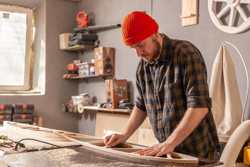 Construction Worker. A young man in a orange hat  carpenter builder in work clothes processing a wooden board with a milling machine in the workshop, around a royalty free stock image