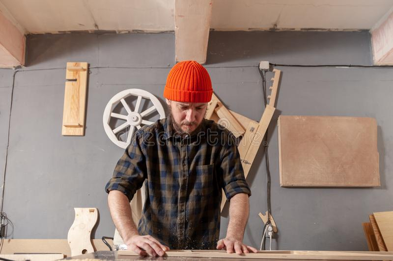 Construction Worker. A young man in a orange hat  carpenter builder in work clothes processing a wooden board with a milling machine in the workshop, around a stock image