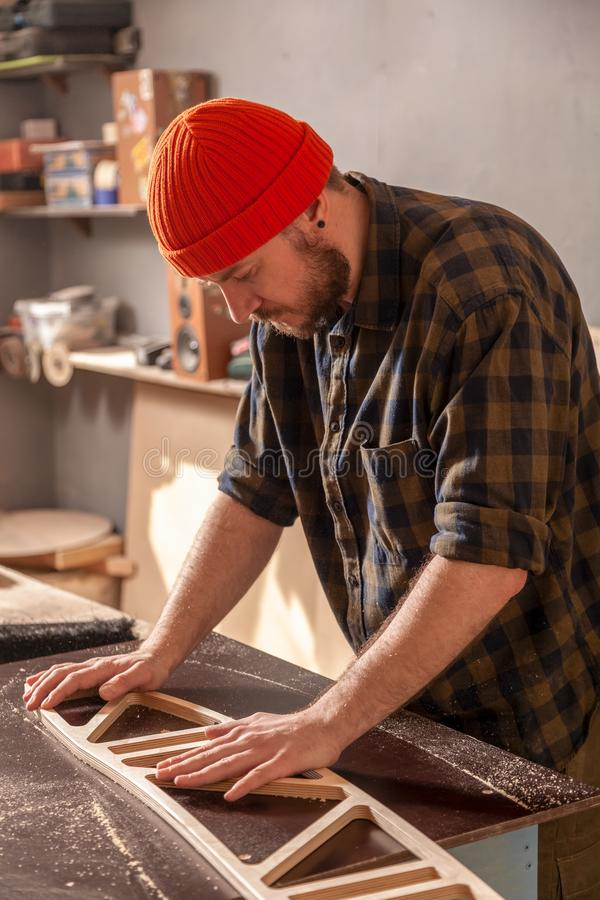 Construction Worker. A young man in a orange hat  carpenter builder in work clothes processing a wooden board with a milling machine in the workshop, around a stock photography