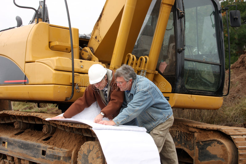 Construction workers with blue prints. Two construction workers study blue prints on work site royalty free stock image