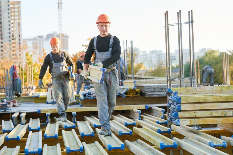 Construction workers at building area installing wormwork royalty free stock photos